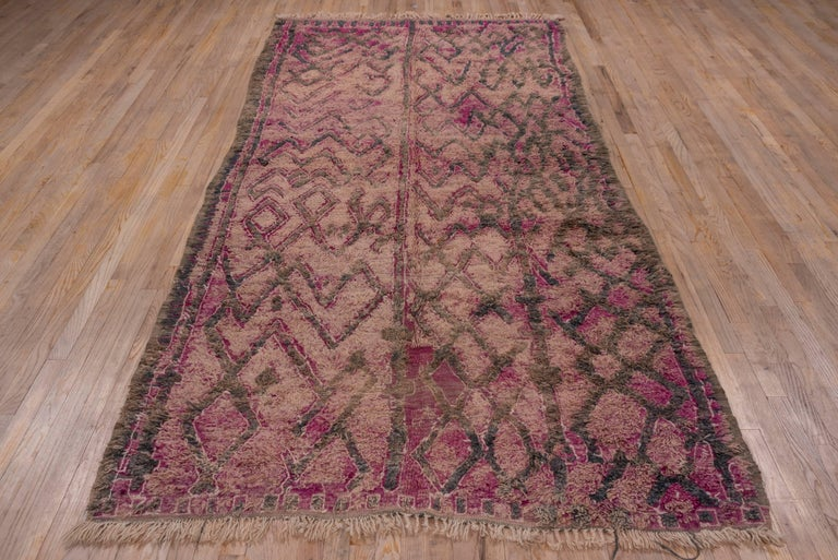 Often used as bed covers or as beds in their own right, these heavy pile wool carpets are thick and exotic. An abstract and vague Primitive pattern adorns this piece which is woven from wool hand-knotted pile on a wool foundation warp and weft.