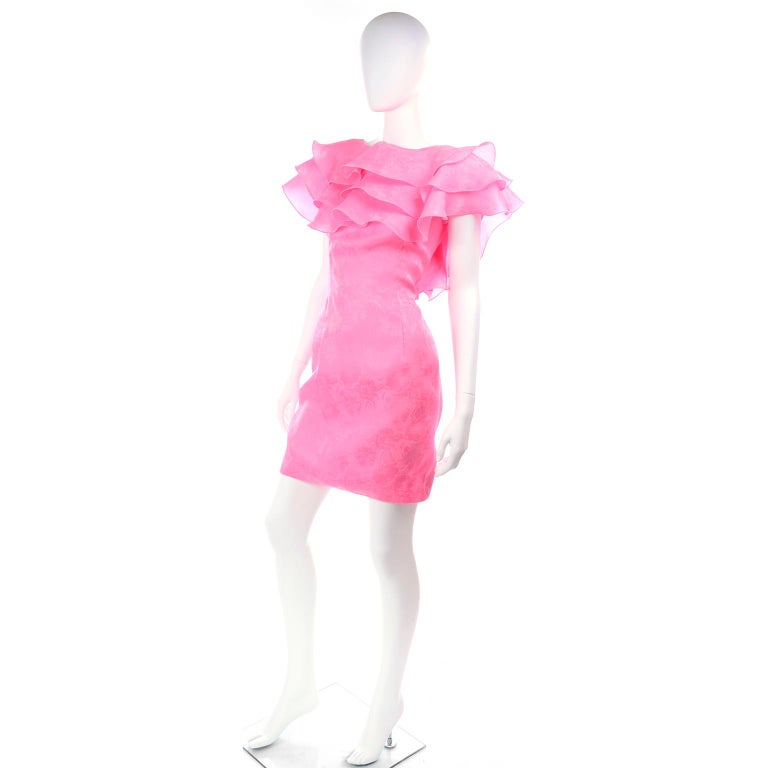 This is a show stopping vintage hot pink dress from Morton Myles purchased at Saks Fifth Avenue in the 1980's. This extraordinary little dress has shoulder pads,  iridescent crystal type buttons in the back and layers of ruffles that flutter across