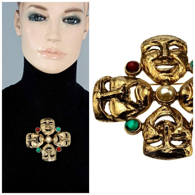 Vintage MOSCHINO Comedy Tragedy Mask Jewelled Novelty Brooch  Measurements: Height: 3.42 inches (8.7 cm) Width: 3.42 inches (8.7 cm)  Features: - 100% Authentic MOSCHINO. - Comedy and tragedy masks brooch with pearl, red and green cabochons. - Gold