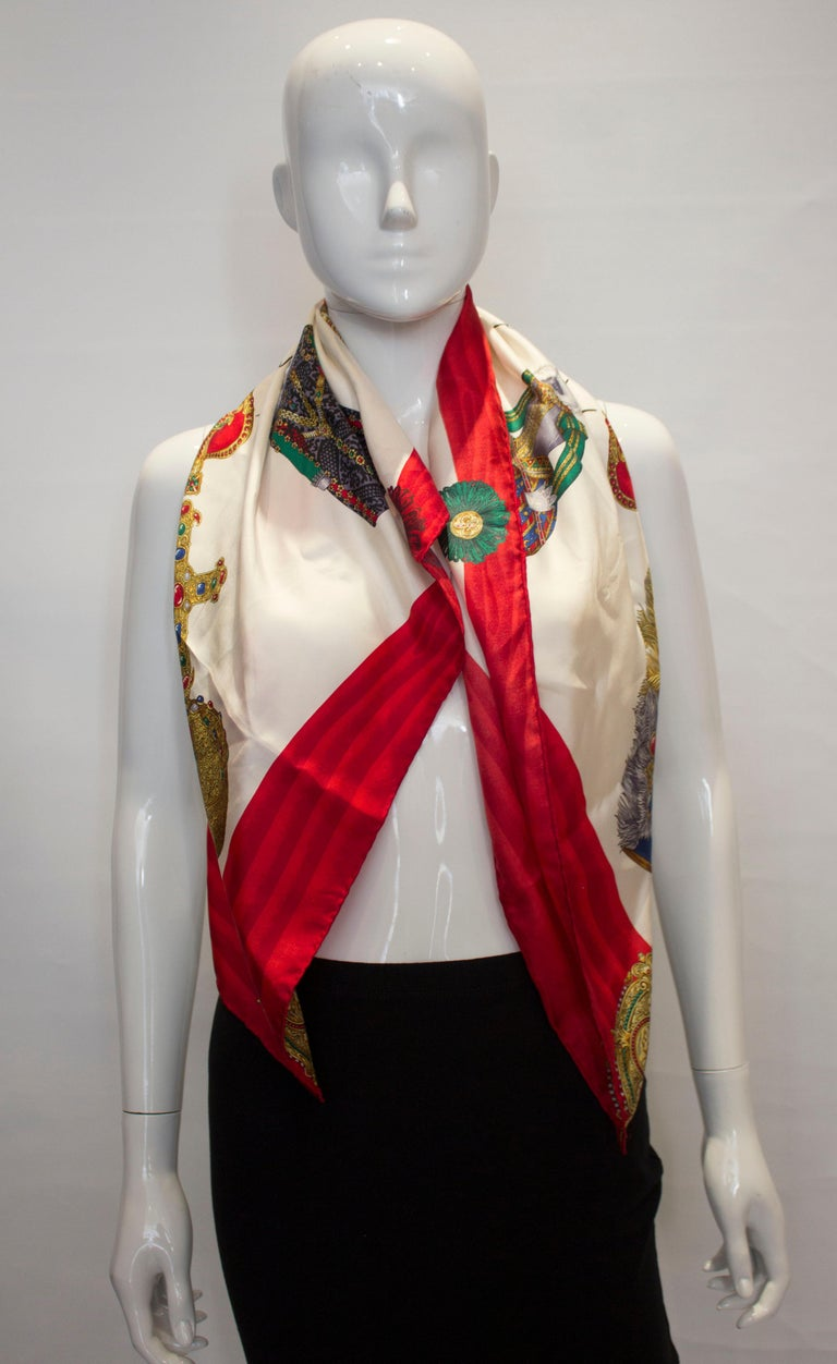 A great gift for Chrsitmas. a vintage hand rolled scarf by Moschino. The scarf has a red border and white centre with crown desgin.