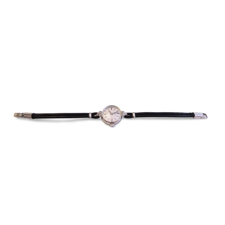 Movado  14K White Gold  Diamond= 0.15 ct total Width Mechanism Black Leather  Dial= 17mm
