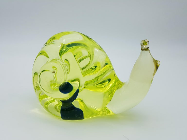 This cute vintage snail was made in the mid-1960s in Murano by the glass-factory Gino Cenedese e Figlio and desigend by Antonio da Ros. The seal is made in vaseline yellow glass, with a inner blue bubble, and is detailed with two upper tentacles.