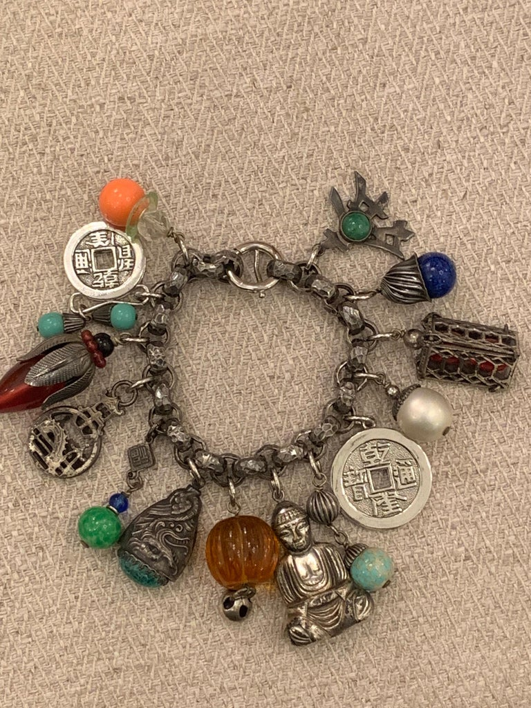 Chunky charm bracelet by Napier - truly a runway showstopper! Asian themed charms...buddhas, lanterns, coins and symbols mixed with multi colored pate de verre drops. SIGNED on clasp - Circa 1950's. 8