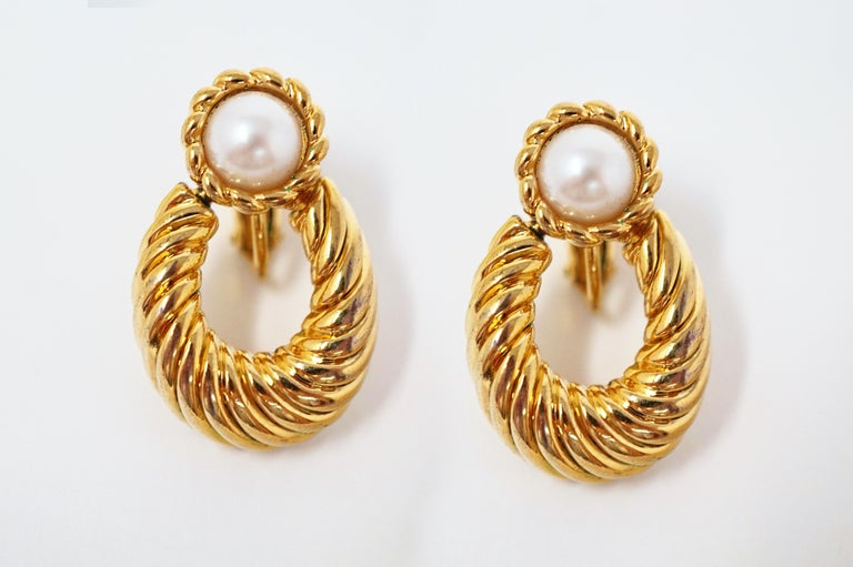 These gorgeous vintage Napier door knocker earrings are a timeless accessory from the coveted costume jewelry brand. A bezel set iridescent faux pearl is surrounded by shiny gold plating in this truly stunning piece. A wonderful addition to your