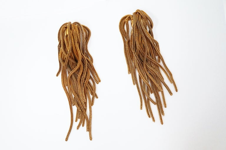 These gorgeous vintage Napier gold fringe clip-on earrings are a timeless accessory from the coveted costume jewelry brand. A single gold-plated bead holds a bundle of gold chain which cascades over itself for a seamless waterfall look. A wonderful