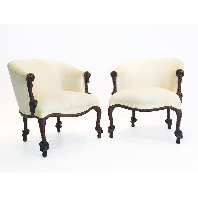 A beautiful pair of carved rope and tassel Napoleon III style painted armchairs. Features a solid carved wood barrel back stained wood frame, Luxurious velvet upholstery. The illusion of twisted and knotted rope is often associated with the work of