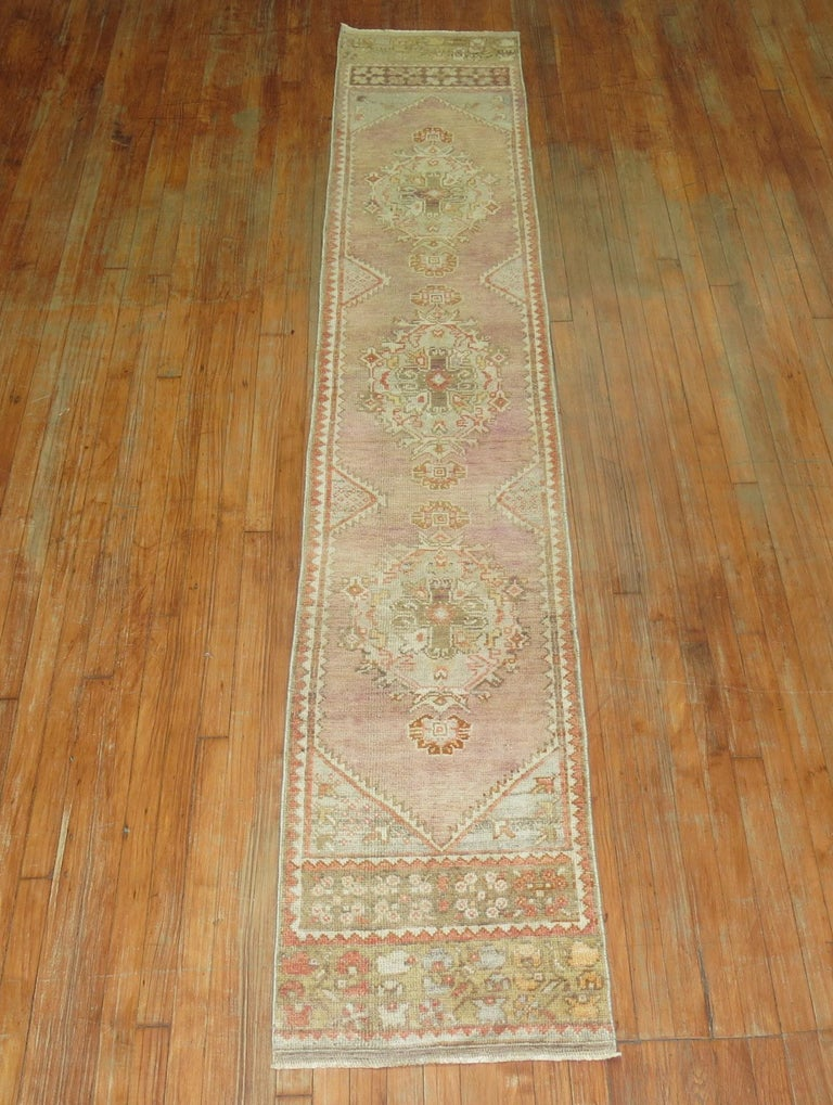 Very narrow one of a kind soft pink vintage muted Turkish Oushak runner.