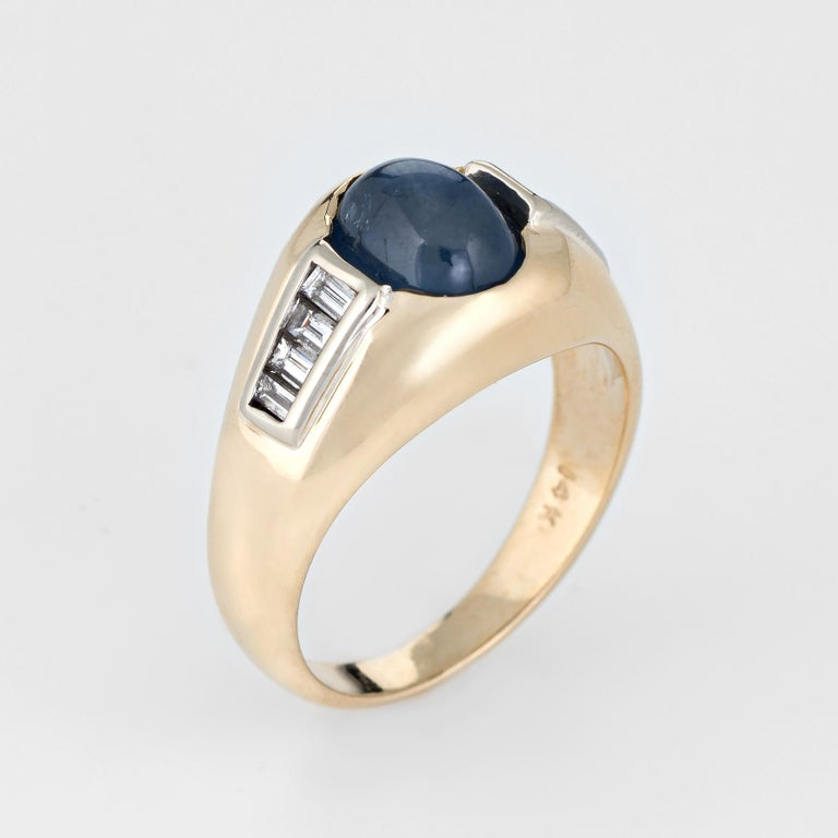 Finely detailed vintage natural sapphire & diamond ring (circa 1980s), crafted in 14 karat yellow gold.   Natural cabochon cut blue sapphire measures 8mm x 6mm (estimated at 3 carats) is accented with an estimated 0.30 carats of straight baguette