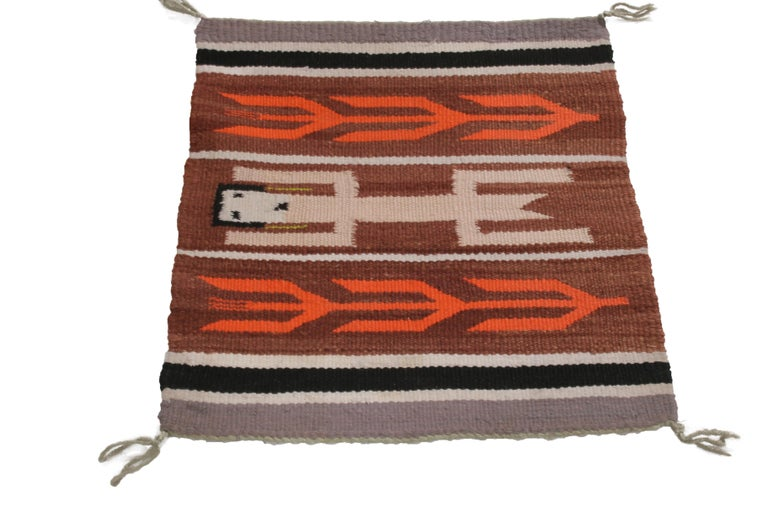 Hand knotted in quality wool from the United States in 1950, this vintage rug employs a marriage of both forgiving and engaging tribal colorways with symbols believed to hail from the Native American Navajo tribe. As one of the largest native tribes