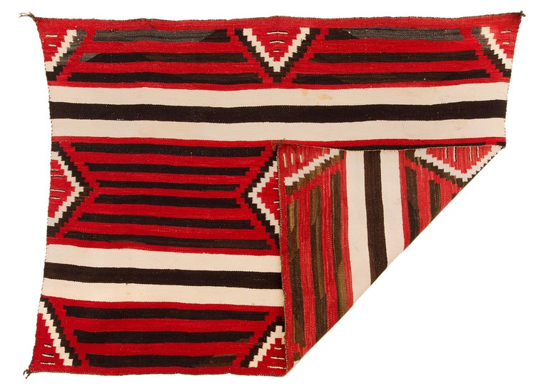 Antique Navajo Chiefs Blanket circa 1900 with a third phase variant design with a nine-point diamond pattern against a banded background. Native hand-spun wool with natural ivory/white and brown/black fleece colors and aniline dyed red. This