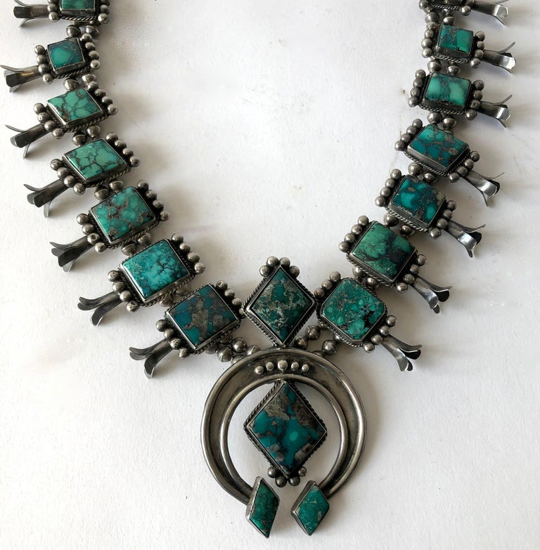 Vintage Navajo squash blossom necklace features a double strand of pearls with large pieces of turquoise, possibly Bisbee, and leaning towards green in color with natural black matrix.  Necklace measures about 26