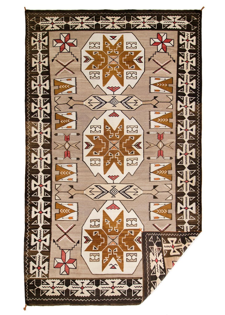 Antique Trading Post rug was woven by a Navajo weaver in a design typical of the Teec Nos Pos Trading Post/Region, native hand-spun wool in natural fleece colors of brown, black, camel and ivory with aniline dyed red. Pictorial elements include