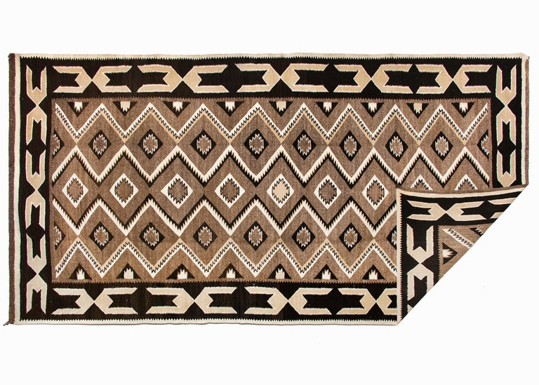 Vintage Navajo area rug in an elongated runner format in a Red Mesa style/pattern, circa 1930s-1950s. Woven by a Navajo weaver of native hand-spun wool in natural fleece colors of brown, ivory and black in a geometric pattern.  Authenticity is