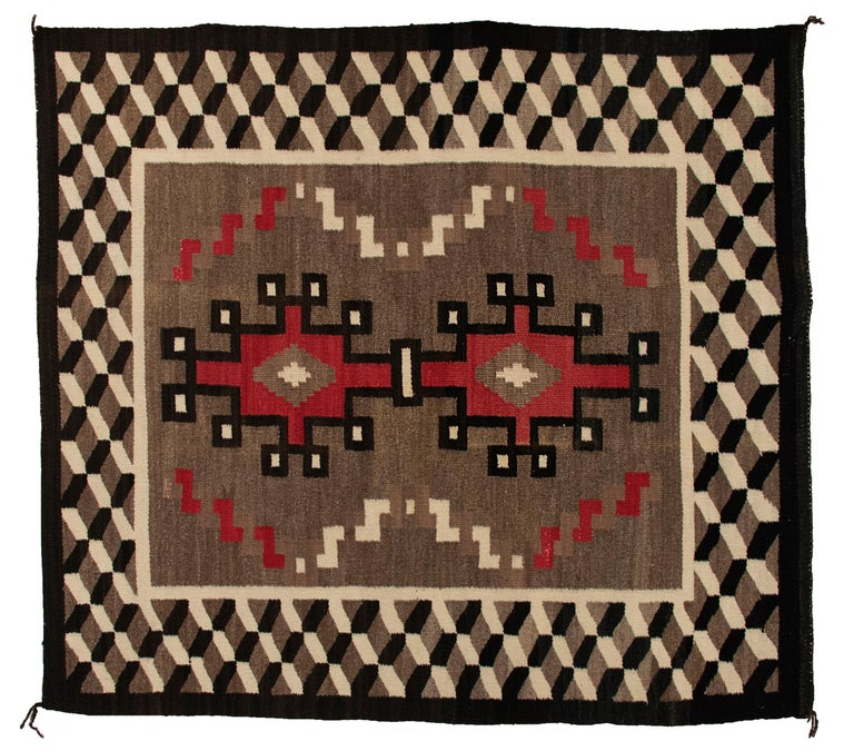 Vintage circa 1940s Navajo rug, handwoven from native hand-spun wool in natural fleece colors of brown/black, ivory and aniline dyed red. Hooked geometric elements are bordered by a tumbling block design. This textile is well suited for use on the