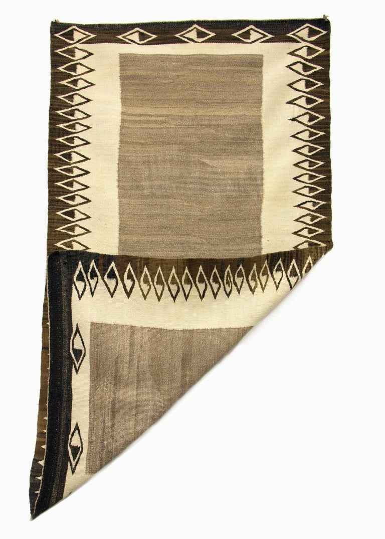 Vintage antique Navajo rug/saddle blanket circa 1900. Woven in a double saddle blanket format of native hand-spun wool in natural fleece colors of ivory, gray and brown/black. This textile is well suited for use on the floor as an area rug or as a