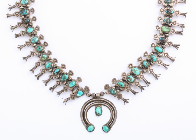 A small scale Navajo Turquoise Squash Blossom Necklace, lacy and refined, was made c. 1930-40 by Eskie Sossie an honored native jeweler. He was the first to create this style of box bow squash blossom. Each link looks like a small bow with a