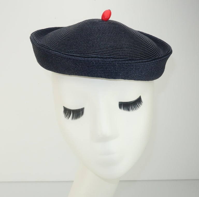 Vintage navy blue straw hat designed with a nod to a sailor's cap.  The addition of a vibrant red bead finial lends an air of whimsy and an overall look that is perfect for nautical inspired ensembles.  Labeled 'Julian Hilton' and lined with a
