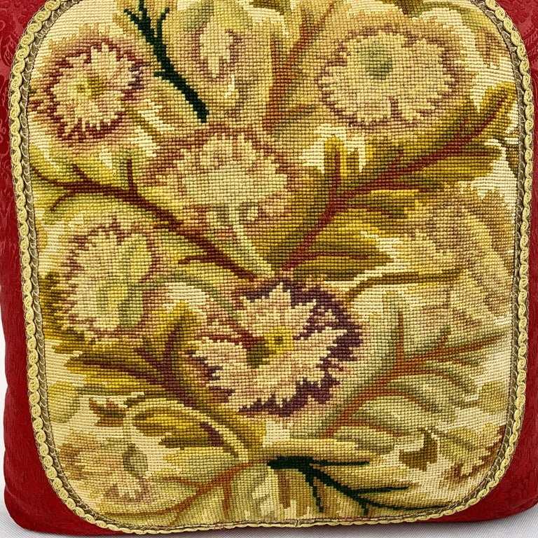 Cushion or decorative pillow of vintage needlepoint. The hand stitched needlepoint is appliqued to the pillow top with passementerie (trim). The new backing is a lush red damask. The stitcher took great effort to match the fabric front and back (see