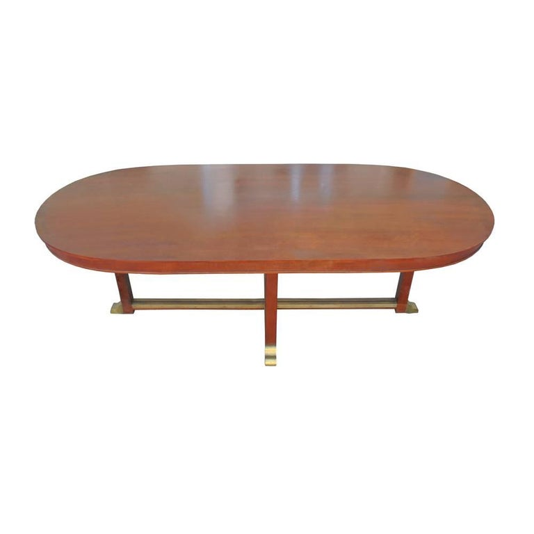Vintage neoclassical style racetrack dining conference table    Classical lines in mahogany with brass details at base and feet.  Racetrack top.