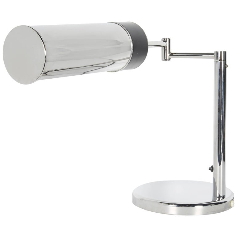 Mid-Century Modern Walter Von Nessen for Nessen studio desk lamp. Features swing arm design and adjustable shade. The lamp has a sleek cylinder shade with circular base in polished chrome and features black enameled metal accent. Fitted with on/off