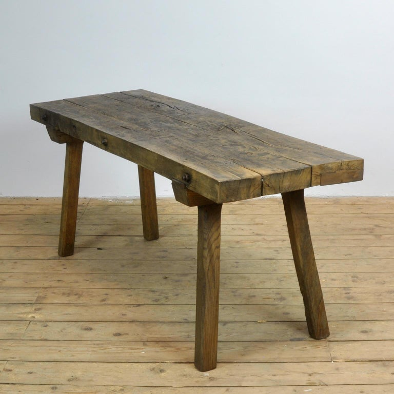 This oak butcher's farm table was produced in Hungary circa 1930s. With a nice distressed oak top of 7 cm thick. This piece features the original legs and has been wax-finished. Treated for woodworm.