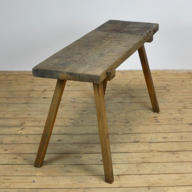 This oak butcher's farm table was produced in Hungary, circa 1930s. With a nice distressed oak top of 6.5 cm thick. This piece has been wax-finished. Treated for woodworm.
