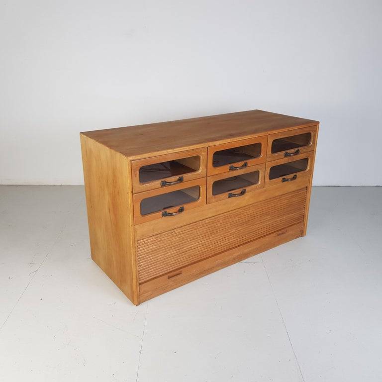 Lovely 6-drawer haberdashery shop cabinet from the first half of the last century.  It has 6 glass fronted drawers, all with original metal D handles and a tambour roll up shutter for the bottom compartment.  Approximate dimensions:  Width 119