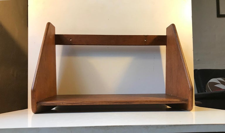 Simplistically constructed wall shelf in solid oak. Designed by Hans Jorgen Wegner for FDB during the 1950s. The is an example dating from this period. The shelf is stamped made in Denmark to the backside.