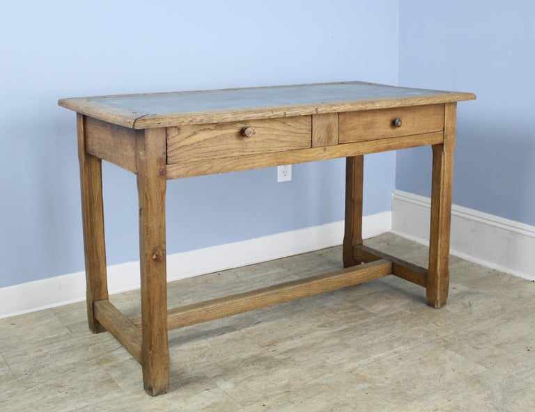 A solid oak writing table with a light gray zinc top. Trestle base is comfortable for resting one's feet. The carved F on the leg (shown in image #4), as well as the colorful interior of the drawers, are evidence of this tables past life in a French