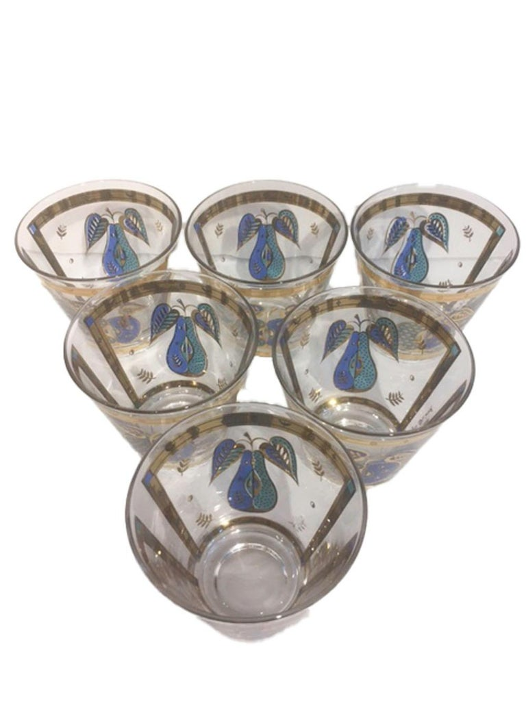 Mid-Century Modern old fashioned glasses by Georges Briard in the Forbidden Fruit pattern. Each of clear glass decorated in translucent blue and green enamel and 22 karat gold. Each glass has a pear on one side and an apple on the other within an