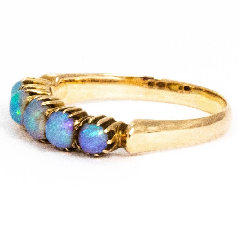 The opals in this five stone band are absolutely magical. They have a gorgeous strong blue hue with flecks of purple, green an so many other colours. The stones are encased in crimped 9ct gold. The centre stone measures 30pts and the outer stones