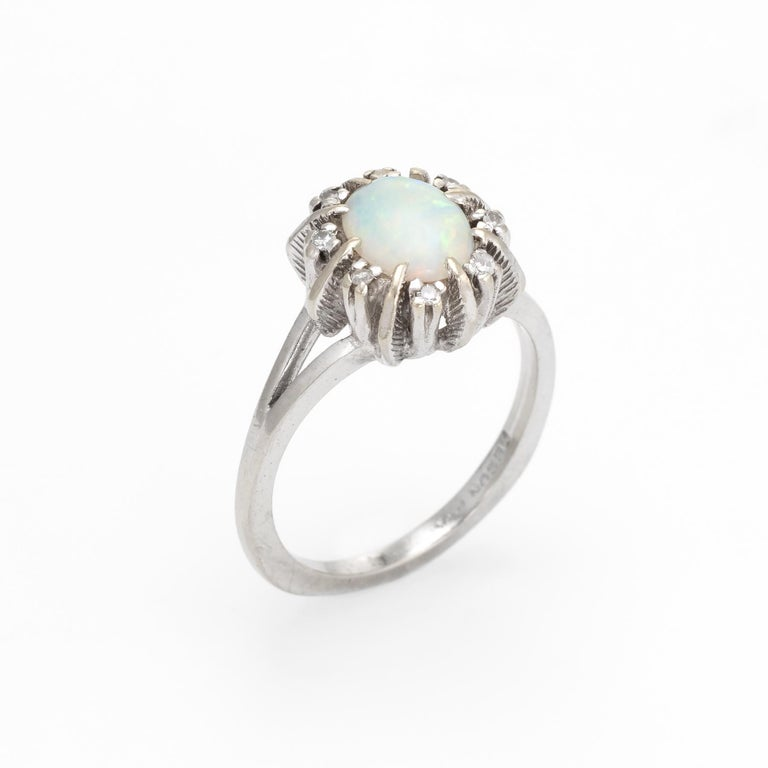 Finely detailed vintage opal & diamond cocktail ring (circa 1950s to 1960s), crafted in 14 karat white gold.   Centrally mounted natural opal measures 7.5mm x 5.5mm (estimated at 1 carat), accented with eight estimated 0.01 carat single cut diamonds