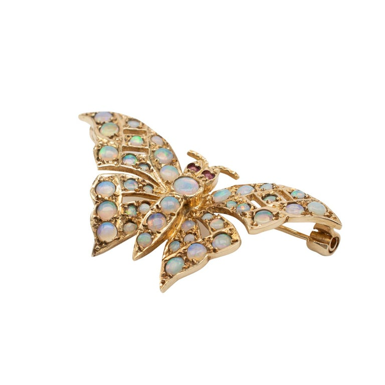 This beautiful vintage gold butterfly brooch, decorated with natural opals is hallmarked London 1985.  The butterfly is realistically sized and looks great adorned into a jacket lapel. The open pierce work gold is ornamented with various sized
