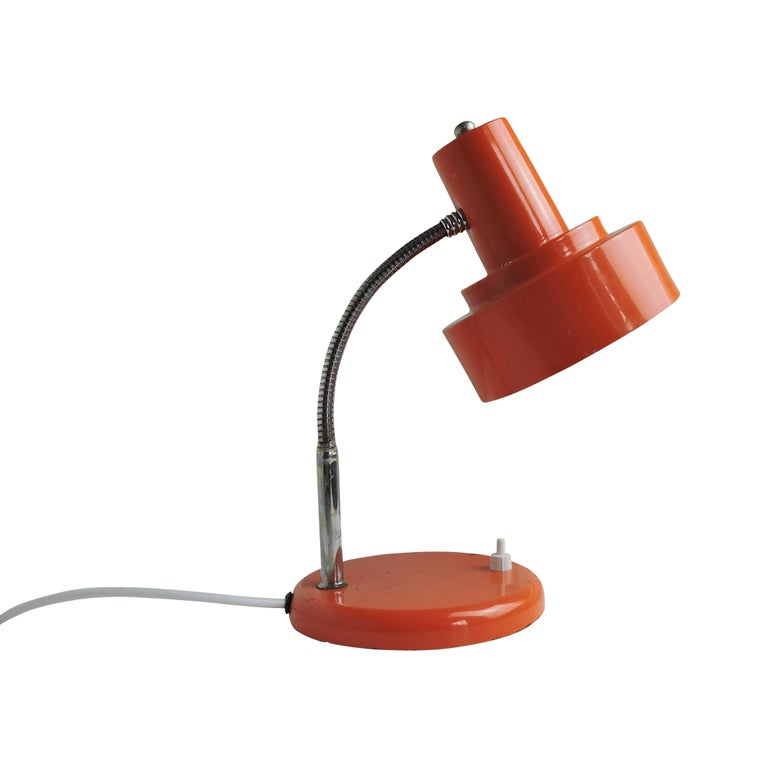 This orange desk lamp features an adjustable lampshade.