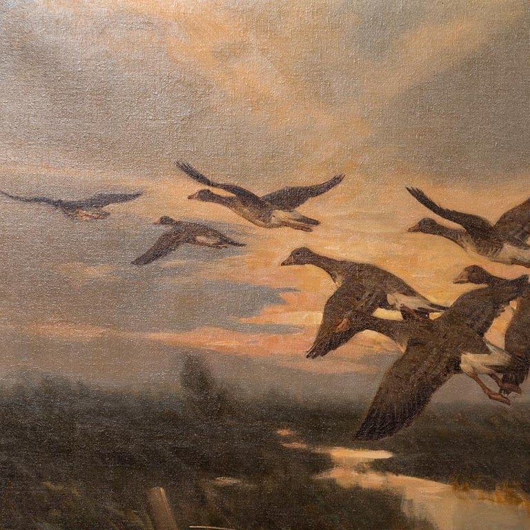 The exceptional detail and use of light evokes the sounds and feel of geese taking flight from a marsh in this original vintage painting. The flock flies through the rays of the rising sun, diffusing the light and highlighting the clouds above and