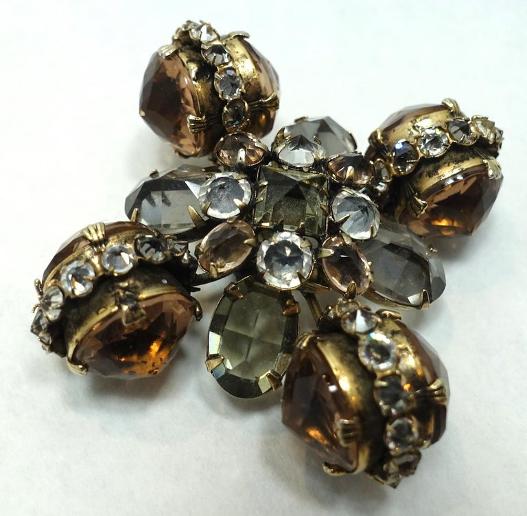 When I first saw this brooch, I thought it might be a Countess Cis … but it has no signature. This vintage brooch can also be worn as a pendant and features an ornate design with topaz, gray and clear color crystals in a gold tone setting.  This