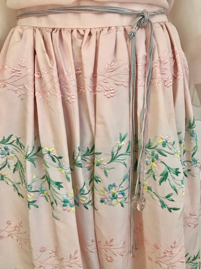 This 1980s Oscar de LaRenta peasant blouse with matching embroidered skirt is the perfect blend of casual, sexy and elegant. The blouse can be worn on shoulder, off shoulder or one shoulder. The heavy silk skirt has beautiful detailed embroidery of