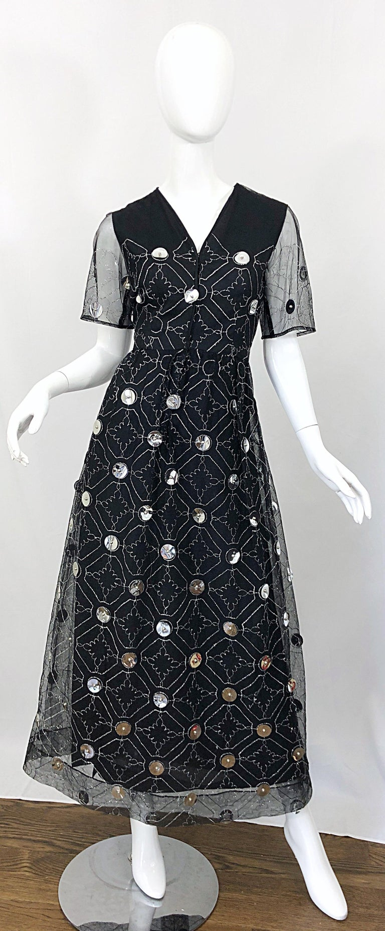 Wonderful early 1970s OSCAR DE LA RENTA black silk and tulle + silver pailletes short sleeve evening gown! Features a sleeveless silk base with black tulle short sleeve attached overlay. Metallic silk embroidery throughout. Hundreds of large