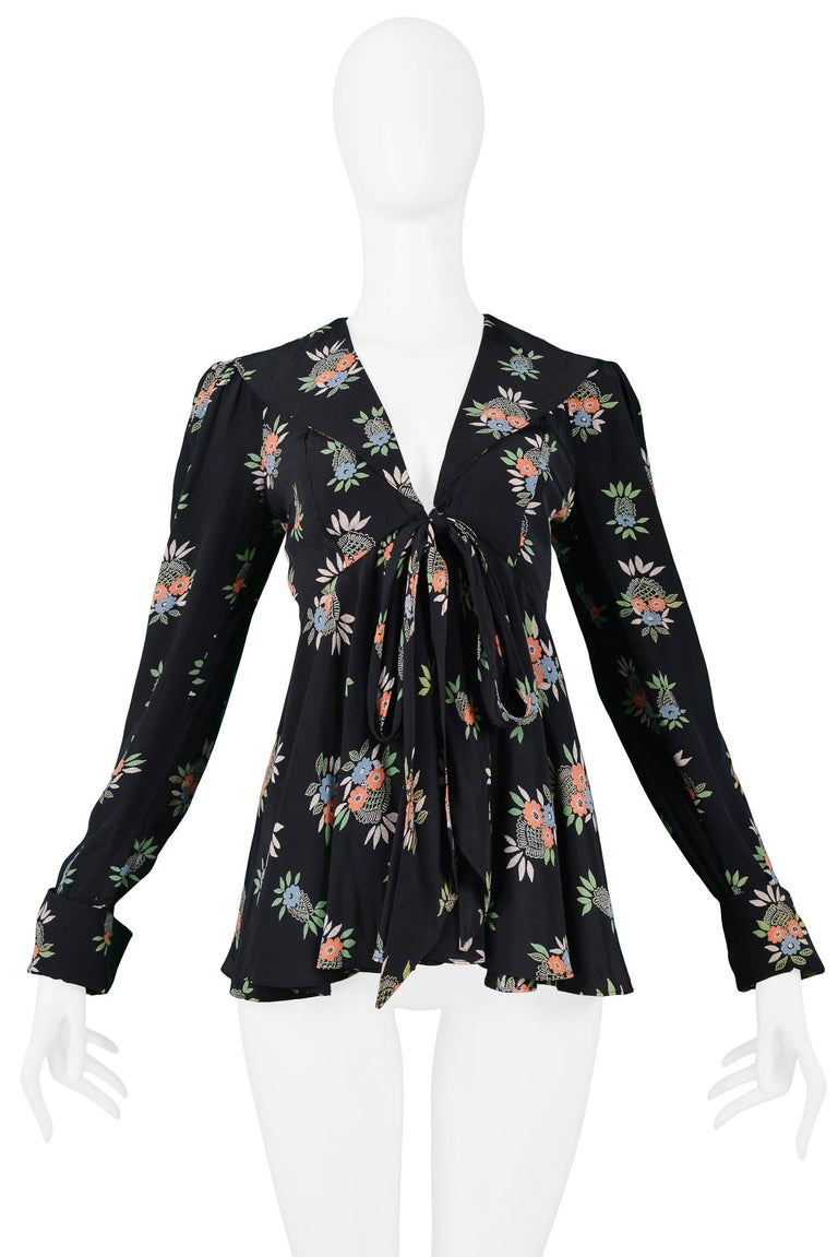 Vintage Ossie Clark black peplum top with Celia Birtwell Flower Basket print. Features a V-neckline, empire waist, and ties at front. Circa 1970s.  Excellent Vintage Condition.  Size: UK 10  Measurements: Bust 30