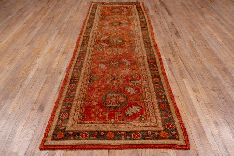 This vintage 1920s Oushak runner has been woven in a village setting by an experienced weaver. At first glance, it may seem the pattern is somewhat random but is actually well balanced. Complimenting the design with an understated palette makes a