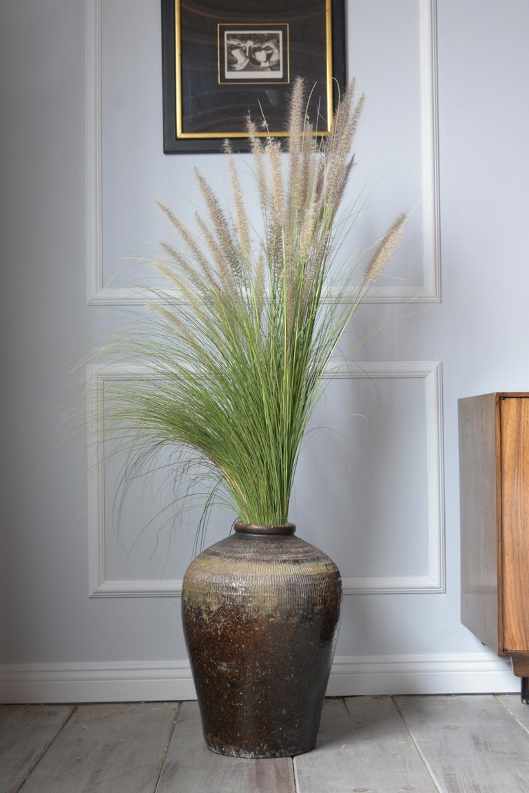 A large ceramic indoor or outdoor vase with carved details on the top urn design beautiful dark brown and green color combination with glazed finish and beautiful patinated.
