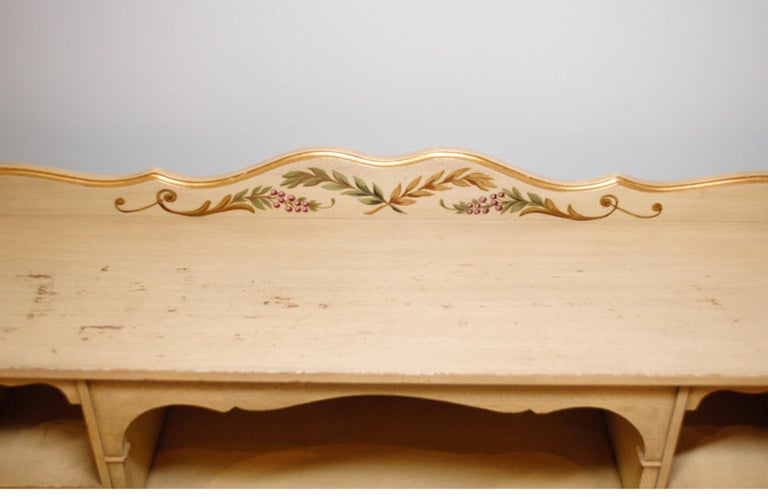 Interesting hand painted writing desk with gallery. The gallery is attached and gives lots of extra storage and display. The solid wood desk has the original hand-painting. The base color is a buttery off-white with natural distressing. The edges