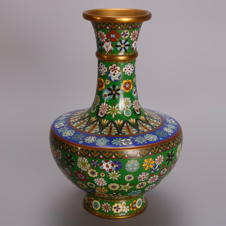 A pair of matching vintage Chinese Cloisonne vases offer urn form with all-over hand enameled floral decoration on emerald green ground with sapphire blue banding, 20th century.  ***DELIVERY NOTICE – Due to COVID-19 we have employed