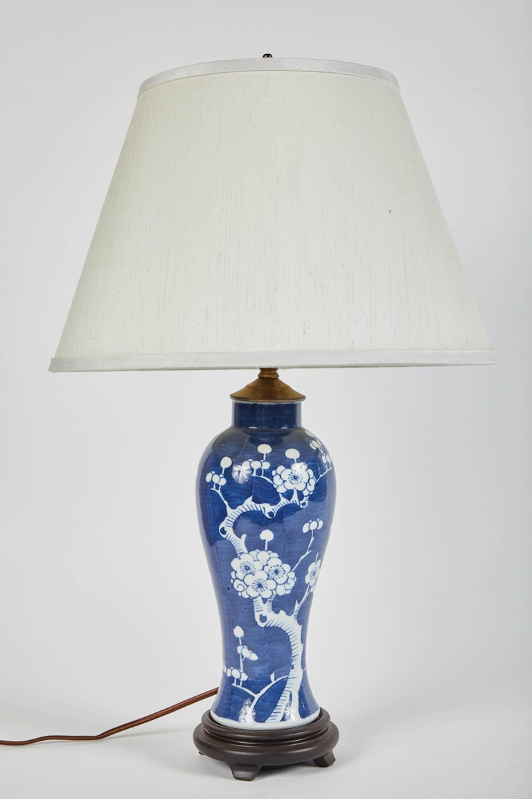 A pair of 20th century blue and white vases featuring cherry blossom motif. Turned into electrified table lamps with ivory shades.