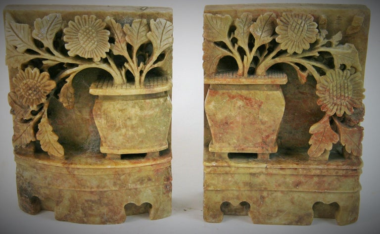 8-166, a vintage pair of Chinese bookends offering deeply carved soapstone with jardinière with draping foliage, circa 1930s.