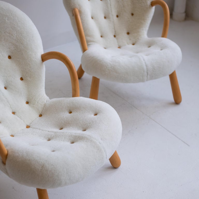 Pair of iconic clam chairs by Philip Arctander newly reupholstered in sheepskin with leather buttons, and wood finish was fully restored recently as well.
