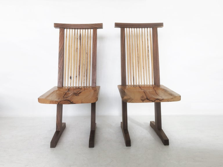 Minimalist elegance! Handcrafted using walnut and hickory conoid chair after George Nakashima. The structure is characterized by the presence of two legs that extend from the feet in the form of a sled, which serve as uprights that support a