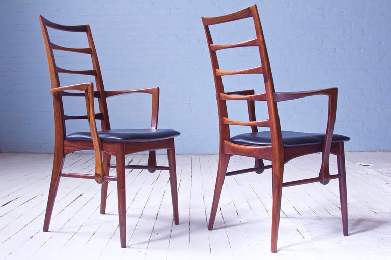 An awesome pair of the supremely elegant 'lis' armchairs in richly figured tropical hardwood and black leather. These frames feature a ladder back stile arrangement borrowed from various vernacular Windsor forms; here however the stiles are