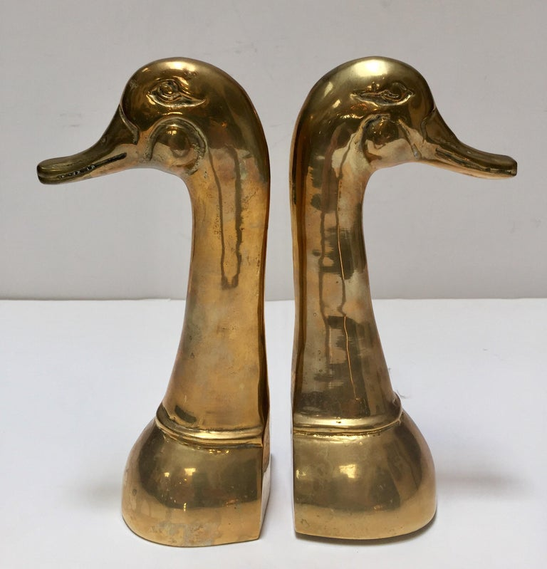 Pair of polished decorative brass duck bookends in Sarried style. Set of midcentury vintage cast metal brass duck sculpture bust bookends. Aged warm glow patina. Size for each is 6
