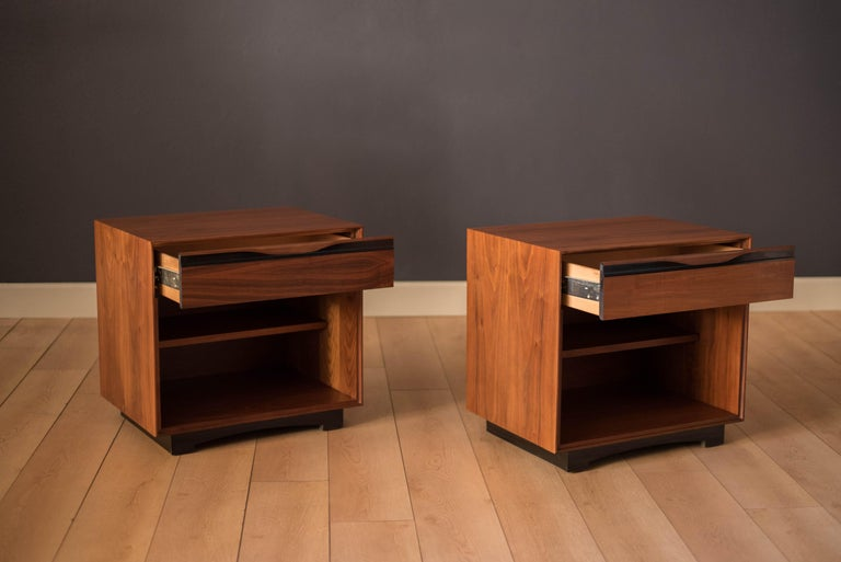 Mid-Century Modern pair of nightstands designed by John Kapel for Glenn of California in walnut. Includes one drawer and an adjustable shelf on each bedside table.    Offered by Mid Century Maddist